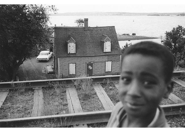 ZP_Young boy with, in the background, Ralph Jones' house boarded up for demolition_Africville, Halifax, Nova Scotia, Canada_1965_photo by Bob Brooks