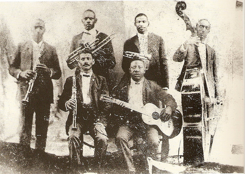 ZP_Buddy Bolden (top row, second from right) and his Orchestra, 1905.   New Orleans native Bolden combined a looser form of Ragtime with Blues, and by adding brass instruments from marching bands to these rhythms and moods he helped to create Jazz.