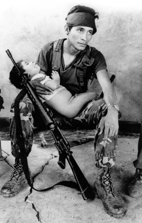 A Salvadorean government soldier with his automatic rifle and a sleeping toddler_after an anti guerrilla manoeuvre in Cabañas province_El Salvador_May 1984