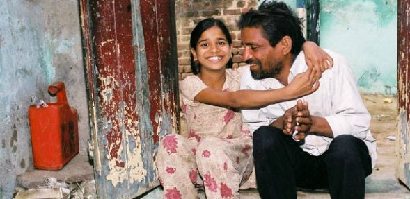 A schoolteacher fired after testing HIV-positive is embraced by his daughter_India_2004_photograph by W. Phillips