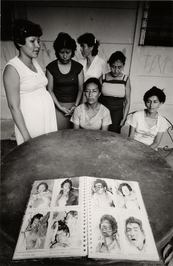 Families looking for quote unquote Disappeared relatives in The Book of the Missing at the Human Rights Commission Office in San Salvador_early 1980s_photograph copyright Eli Reed