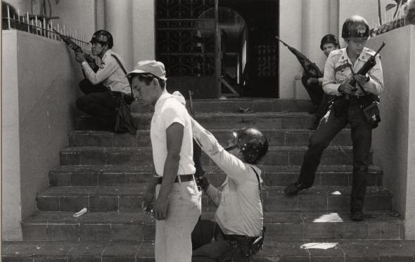 National Policemen using an ice-cream vendor as a shield during a skirmish with demonstrators_San Salvador_early 1980s_photograph copyright Etienne Montes