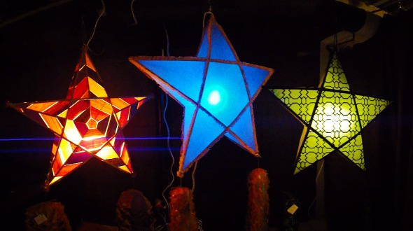 The Parol or Paritaán, is the Christmas lantern of the Philippines.  Often constructed of bamboo and paper, it is now made of many materials.  Originally candle-lit, electric lights – bulbs or LED in a garland – are used now in a variety of colours.  The Parol's design is star-shaped – meant to evoke the Star of Bethlehem that guided the Three Wise Men/Kings to the Christ-Child's Manger.  The Parol also symbolizes hope and goodwill / the victory of light over darkness. These three Parols were made by Kat Estacio, Caroline Mangosing and Katrina Estacio at the Kapisanan Community Centre, Toronto, Canada.