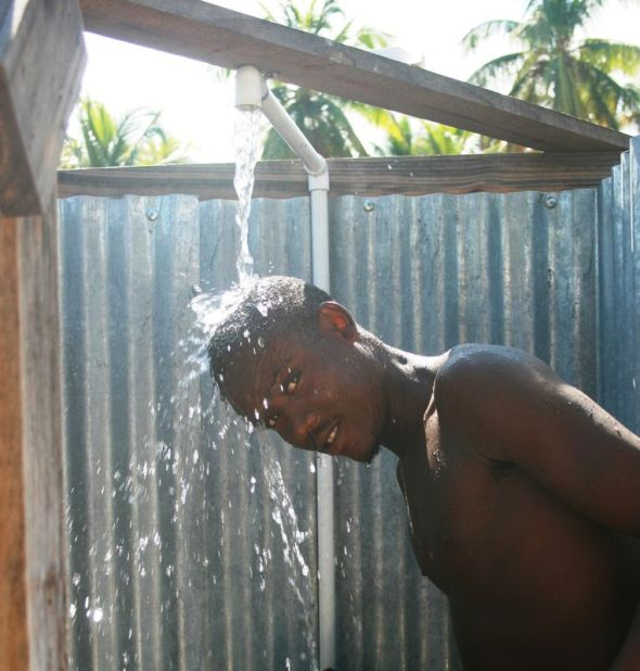 A young man bathes at a public shower in Petit Goâve, Haïti