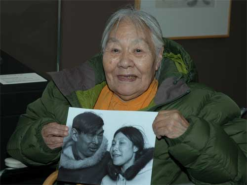 Kenojuak in 2009, holding a 1968 photograph of herself with husband Johnniebo Ashevak