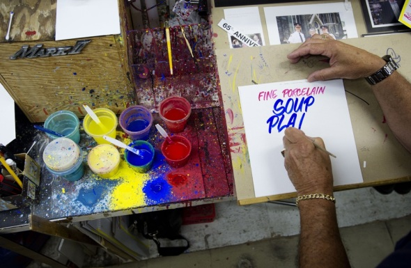 Honest Ed's signpainter, Wayne Reuben, at work in July 2013_photograph by Darren Calabrese, National Post