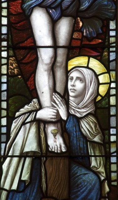 Mary Magdalen at the foot of The Cross as Jesus suffered_an 1886  stained glass window from Saint Bledrws Church in Wales