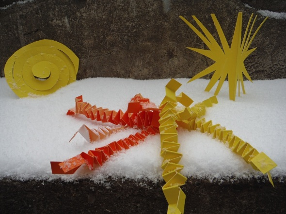 Paper cutouts yellow and orange on stone steps in the snow_Toronto Canada
