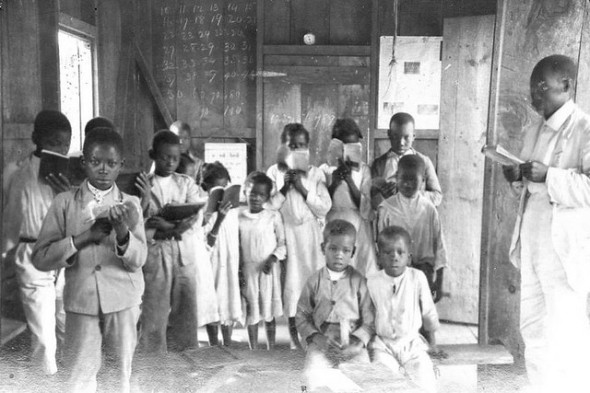 Jamaican primary schoolhouse with children and their teacher_early 20th century photograph