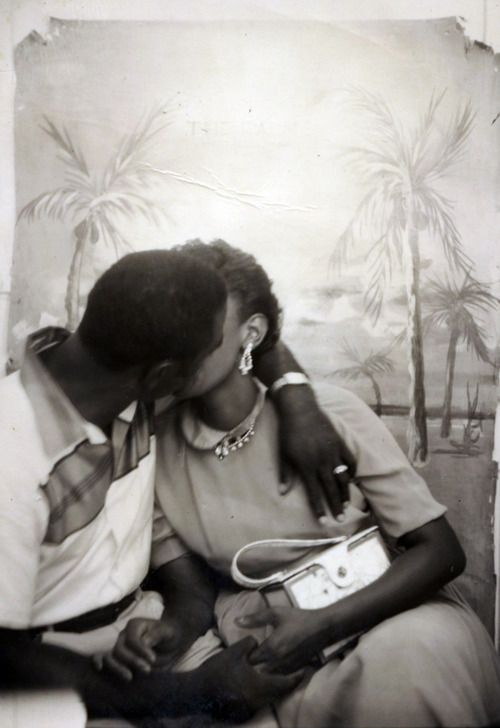 Vintage photograph for Valentines Day_African American couple kissing during a photography studio portrait taking