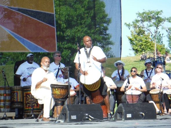 Muhtadi Thomas, seated at front left, performs with his World Drummers ensemble at Woodbine Park in Toronto_June 4th, 2016